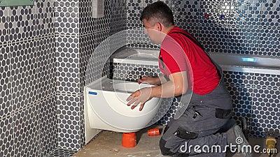 Un plombier souriant à la caméra et montrant le doigt assis sur le bol de toilette clips vidéos
