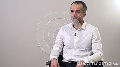 Un portrait rapproché d'un bel homme caucasien de premier plan aux yeux bruns parlant devant la caméra Attrayant mec assis au banque de vidéos