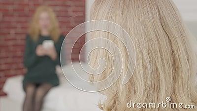 Un portrait rapproché d'une femme caucasienne mature retournant la tête pour regarder son amie et regarder la caméra banque de vidéos
