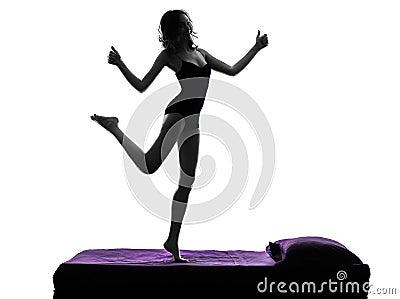 Pulgar feliz de la mujer que se levanta en silueta de la cama