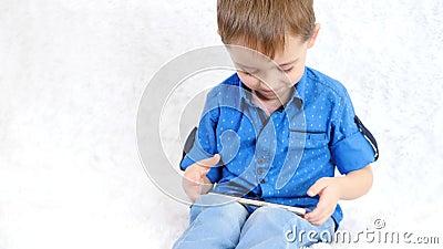 Un ragazzino gioca un gioco educativo attraverso Internet Il bambino esamina lo schermo dello smartphone e delle risate archivi video