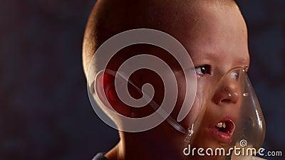 Un ragazzo caucasico biondo inala coppie con medicinali per smettere di tossire Procedure mediche Inalatore Medicina respiratoria archivi video