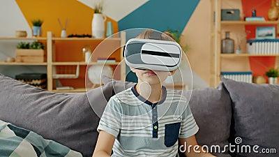Un ragazzo felice usa occhiali di realtà virtuale che si guardano intorno gestendo seduti in un appartamento video d archivio