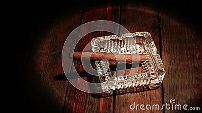 Un sigaro giace in un posacenere su un vecchio tavolo di legno in un raggio di luce. Panorama archivi video