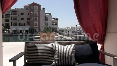 Un sofà vuoto ed ondeggiare nelle tende del vento in un caffè di estate nell'aria aperta video d archivio