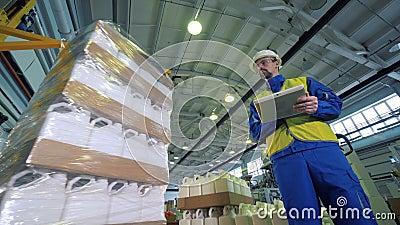 Un supervisore sta osservando i recipienti di plastica ottenere avvolto in cellofan stock footage