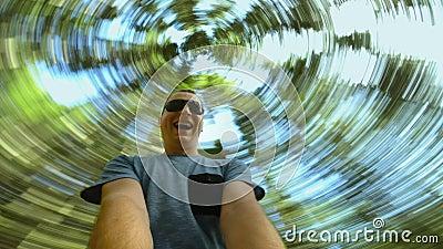 Un tipo curioso y alegre de turista caucásico rota y gira en el bosque, sonrisas y gritos Vista inferior y imagen en ángulo bajo  almacen de video