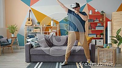 Un tipo giocoso che canta in telecomando a casa con occhiali da realtà aumentati video d archivio