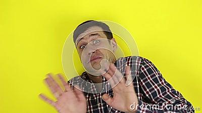 Un tipo gracioso y guapo expresa su miedo y alza sus manos lejos del peligro Retrato de fondo amarillo metrajes