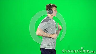 Un tipo guapo con grandes audífonos está corriendo, Chroma Key Vista lateral metrajes