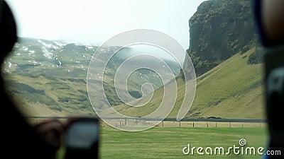 Un touriste qui prend une vidéo du paysage islandais vue par téléphone depuis un bus intérieur banque de vidéos