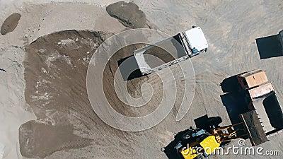 Un tracteur charge des machines avec des pierres écrasées et du sable clips vidéos