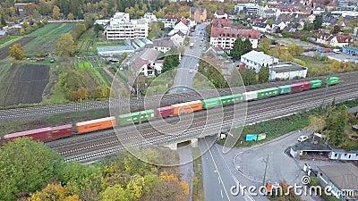 Un train de marchandises chargé de conteneurs traverse la banlieue verte d'Augsburg Oberhausen banque de vidéos