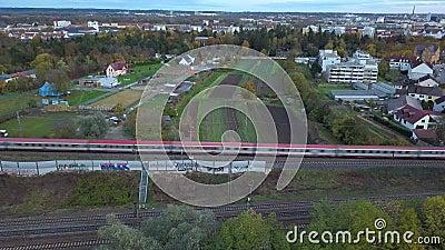 Un train de voyageurs rouge traverse la banlieue verte d'Augsbourg banque de vidéos