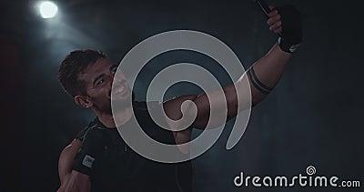 Un uomo atletico e sorridente prende dei selfie con il suo smartphone dopo il duro allenamento in una classe di cross-fitness stock footage
