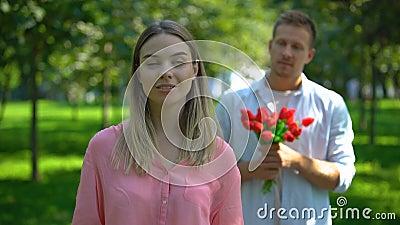 Un uomo che porta un mazzo di fiori, una signora infastidita che arrotola gli occhi, amore non corrisposto stock footage