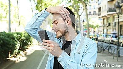 Un uomo che usa un telefono come specchio per comporsi stock footage