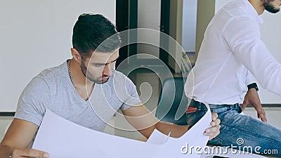 Un uomo con disegni in mano è assorbito nello studio e nella creazione Concentrarsi sul processo senza prestare attenzione archivi video