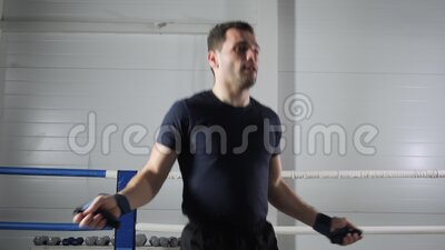 Un uomo da combattimento che si riscalda con la corda saltellata sull'anello di boxe Esercitazione di atleta con corda di lancio  archivi video
