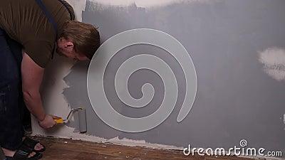 Un uomo forte con un rullo dipinge il muro di vernice grigia archivi video