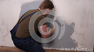 Un uomo forte con un rullo dipinge il muro di vernice grigia stock footage