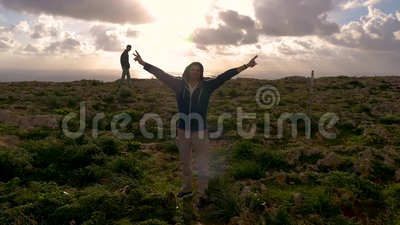 Un uomo in maglia con cappuccio blu alza le sue armi contro il contesto della natura, delle rocce, del mare, del muschio verde e  stock footage