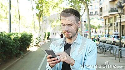 Un uomo sospetto che ti guarda al telefono stock footage