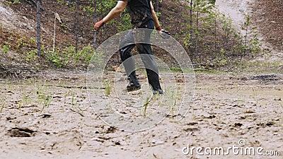 Un uomo in una corsa sporca sta camminando in una pozza fangosa archivi video