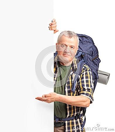 Un viaggiatore con zaino e sacco a pelo maturo che gesturing su un comitato bianco