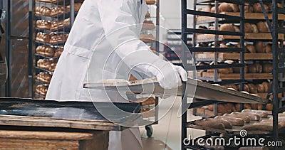 Un vieil homme boulanger en uniforme blanc charge l'étagère de la pâte à transporter vers d'autres sections de la boulangerie, gr clips vidéos
