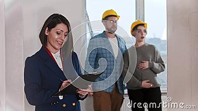 Una agente inmobiliario confiada mujer firma papeles y sonríe en el departamento - pareja joven casada mirando alrededor metrajes