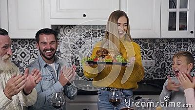 Una bella donna con un maglione a maglia che porta il tacchino arrosto al tavolo festivo dove sta seduta tutta la sua famiglia stock footage