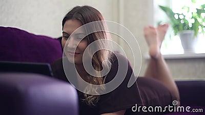 Una bella ragazza sta trovandosi sullo strato e gode di una compressa che muove le sue gambe HD Stile domestico stock footage
