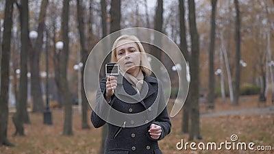 Una bloguera dispara una cámara de acción mientras camina en un parque otoñal almacen de metraje de vídeo