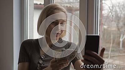 Una bloguera habla sobre negocios y finanzas haciendo videos en línea en un smartphone En la mano de la mujer hay una varita almacen de video