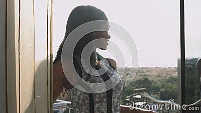 Una chica joven de piel morena elegante se coloca en el balcón y admira la visión almacen de metraje de vídeo