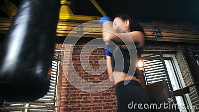 Una chica profesional de combate mma delgada con el cuerpo perfecto haciendo ejercicio en el estudio de boxeo de loft almacen de metraje de vídeo