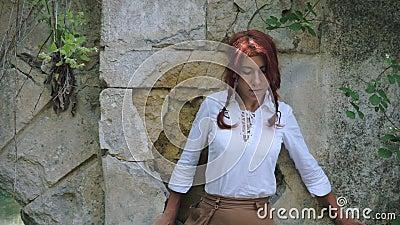 Una chica vestida de pueblo medieval camina por una cornisa a lo largo de la pared de la fortaleza almacen de metraje de vídeo