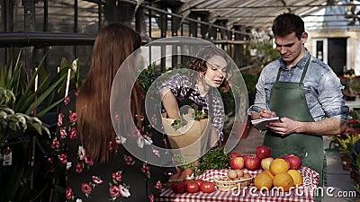 Una commerciante allegra con suo marito sta mettendo il prezzemolo fresco in sacchetto di carta al cliente che parla di mercato i stock footage