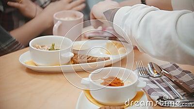 Una coppia al bar a pranzo - cameriere porta loro un ordine e sta per mangiare il porridge stock footage