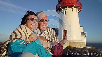 Una coppia matura ammira il tramonto sulla costa di mare con un vecchio faro stock footage