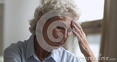 Una donna anziana e triste preoccupata per i problemi di salute a casa stock footage