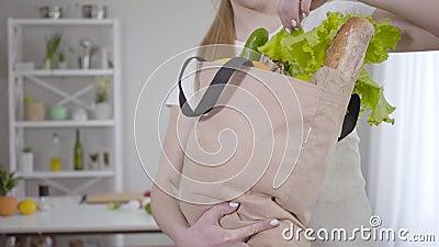 Una donna caucasica sconosciuta tiene una borsa con foglie fresche di insalata, pane e frutta Giovane signora irriconoscibile in  stock footage