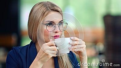 Una donna d'affari molto bella che beve caffè da una tazza rilassante godendosi la rottura media stock footage