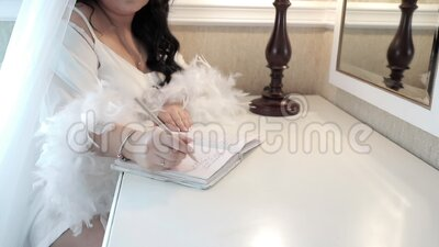 Una donna scrive una nota con una penna, vestita di camicia bianca decorata con piume. stock footage