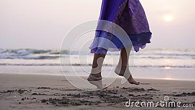 Una donna sta ballando una danza orientale sulla spiaggia al tramonto stock footage