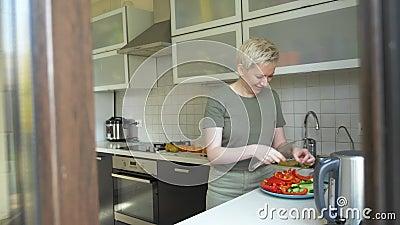 Una donna taglia verdure per uno spuntino in cucina a casa stock footage
