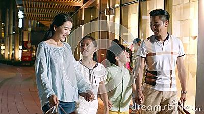 Una famiglia asiatica di 4 che cammina & che compera fuori di un centro commerciale alla notte al rallentatore video d archivio
