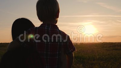 Una familia feliz. Mamá e hijo viendo la puesta de sol. Viajar y caminar al aire libre. El concepto de felicidad y salud almacen de metraje de vídeo