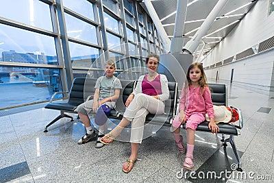 Una familia que se sienta en zona de recreo en el aeropuerto